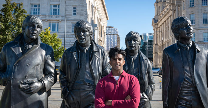 A student stood infront of a statue of the beatles, smiling.