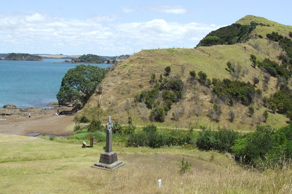 Rangihoua pā overlooking the Oihi mission site on the terrace in the foreground; the monument celebrates Marsden's first Christian service on New Zealand soil.