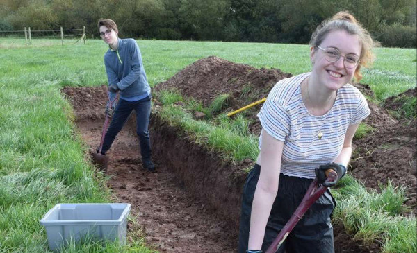 Two students digging