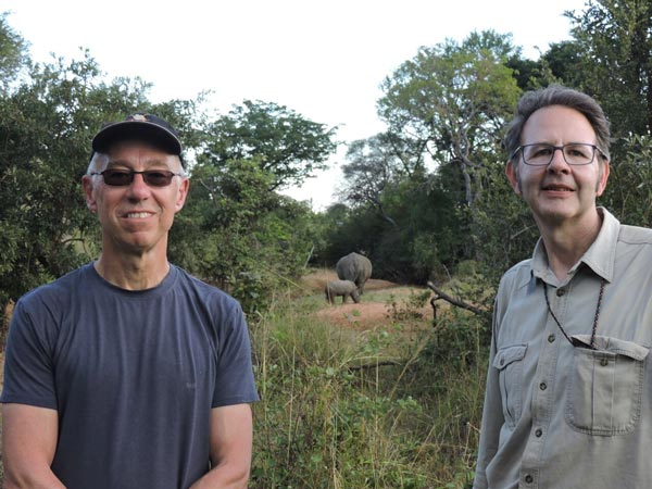 Two men in Zambia, rhinos behind