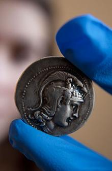 A student holding a silver Roman coin