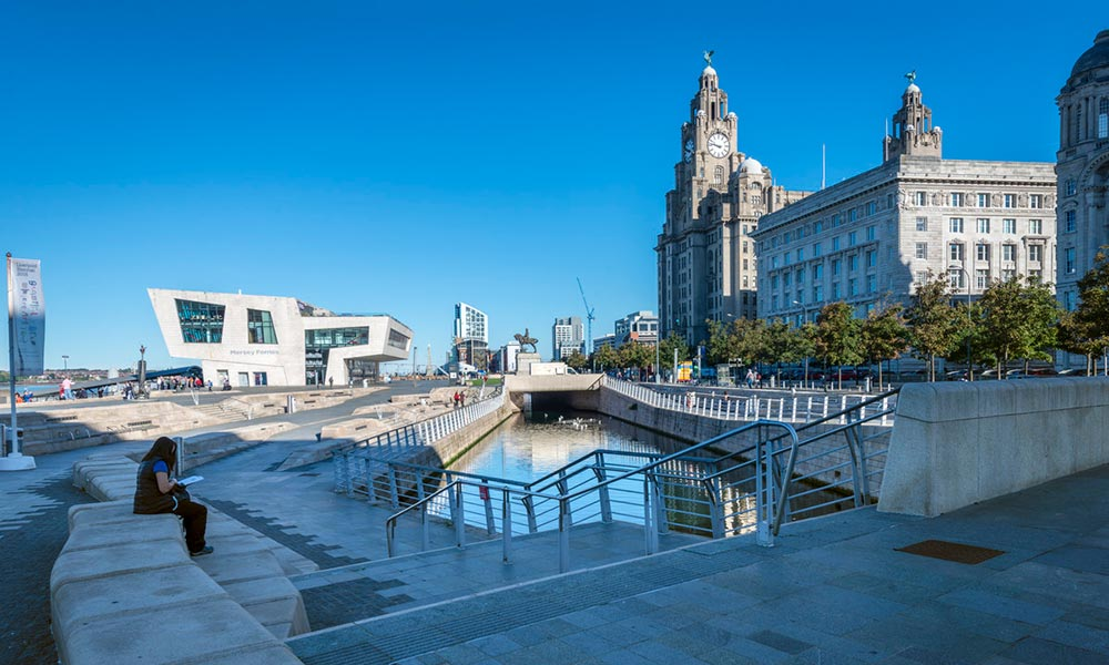Person sitting alone by a canal in front of the Liver Buildings