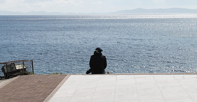 A refugee is looking back towards the shores of Turkey where he came from.