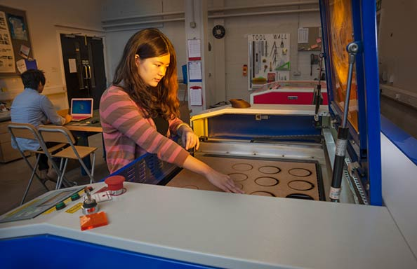 Image of student using laser cutter