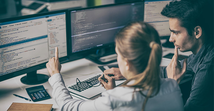 Man and a woman looking at code on computer screens