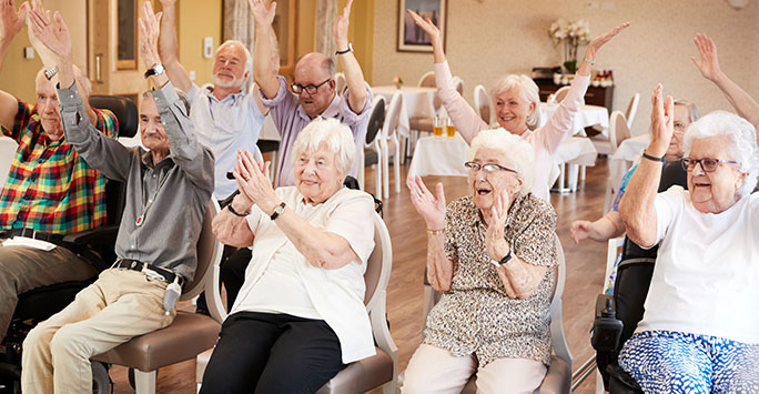 group of elderly people doing chair exercises