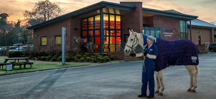 Veterinary surgeon with horse in front of the Equine Hospital reception building