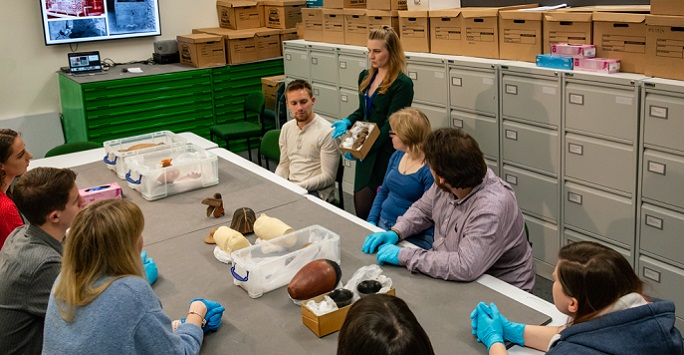 Students in object handling session in The Garstang Museum of Archaeology
