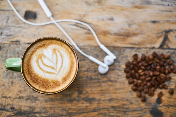 Mug of coffee and headphones on wooden table.