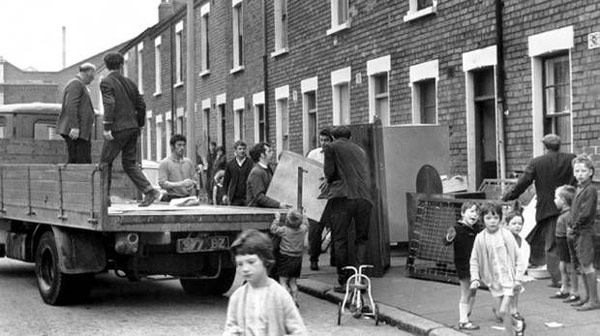 Black and white photo of people unpacking belongings