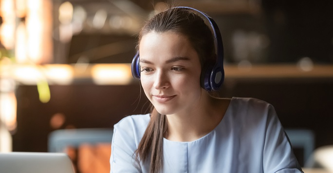 Student with headphones looking at language resources on a laptop