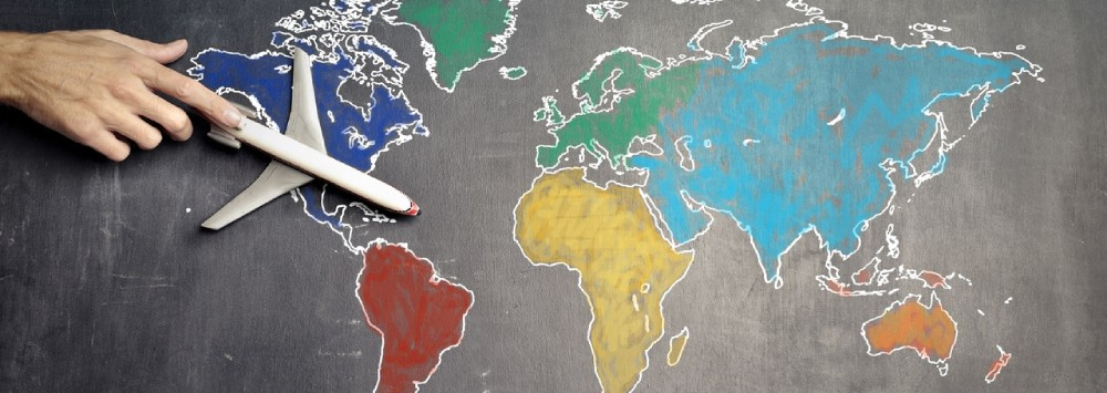 Person with toy aeroplane on world map (Andrea Piacquadio, Pexels)