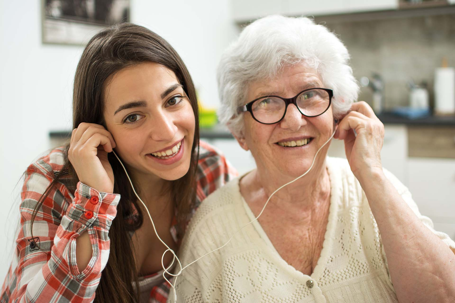 Girl and grandmother listening to music together