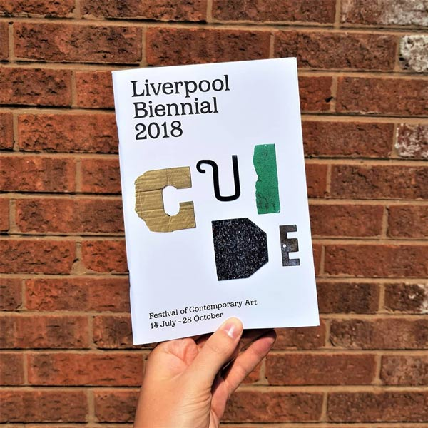 Someone holding the Biennial Guide with an exposed brick background