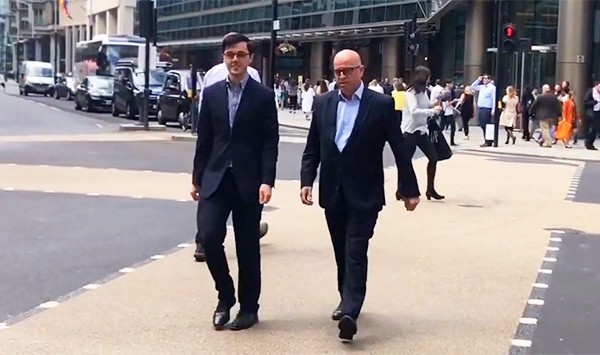 Two men walking across road in suits