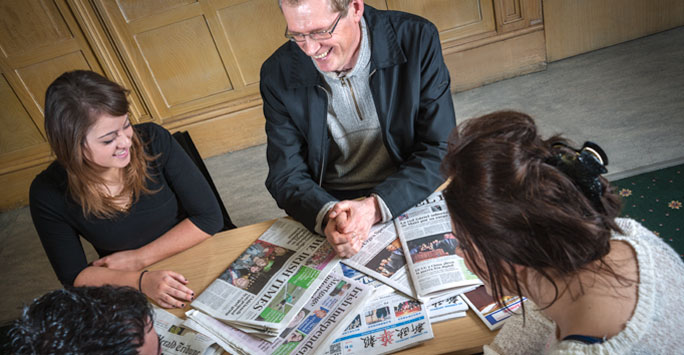 Professor Jon Tonge with students reading newspapers