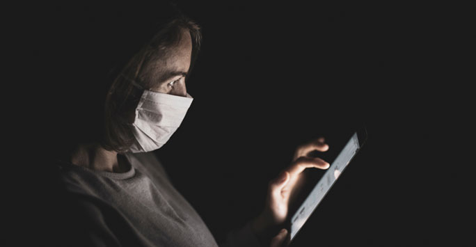Woman in medical mask using mobile phone