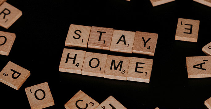 Scrabble tiles spelling 'stay home'