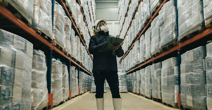 Person wearing a mask between warehouse shelves