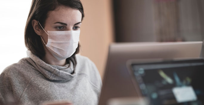 Woman wearing a medical mask writing on a laptop