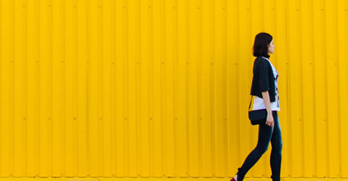 Woman walking against a yellow background