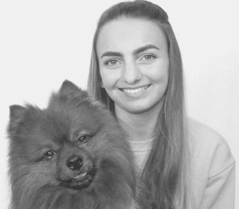 Greyscale imagd of white female with long brown hair, pictured with her red Pomeranian dog