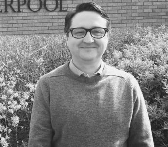 Greyscale image of white male with short dark hair wearing glasses