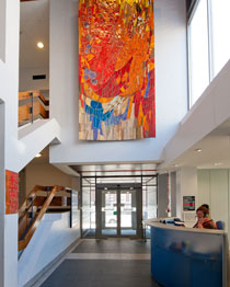 Female dental tutors in foreground wearing green dental scrubs demonstrating dental procedure on phantom head to female student in the background