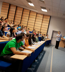 A number of dental student sitting in the school lecture theatre having a lecture delivered by a female member of staff standing at the front of the lecture theatre