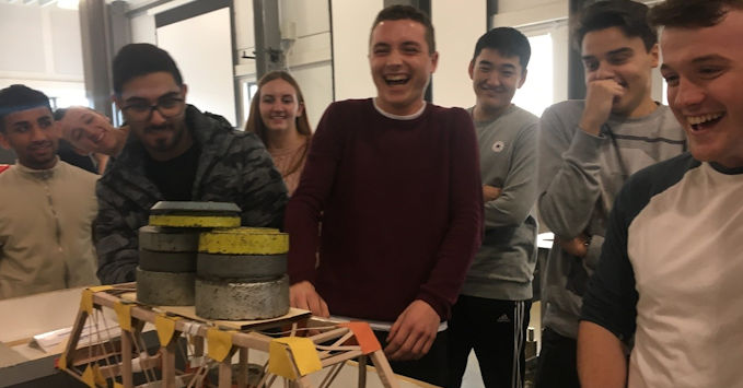 First year students building and then nervously testing to destruction their cardboard bridges as part of the Civil and Architectural Engineering Project