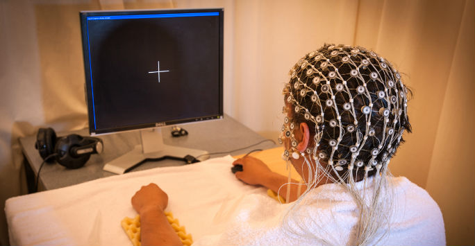 A particpant in a pschology experiment wearing a headset and using a computer