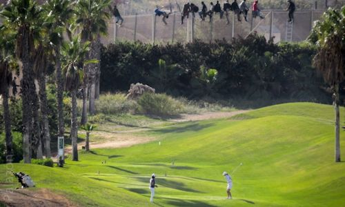 Migrants climbing over a golf course fence in Southern Spain. Should we let them and help them? They are clearly in need and we are clearly affluent (compared to them).