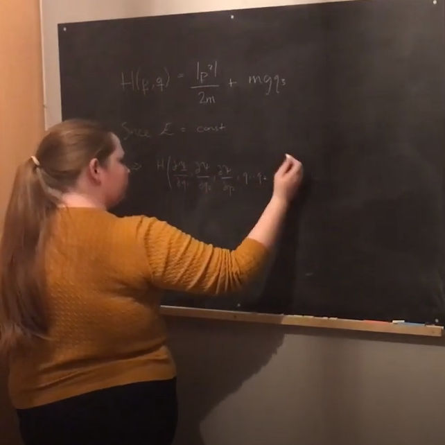 Rebecca writing maths formulas on chalk board