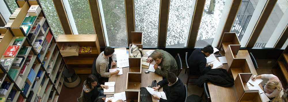Rows of students studying in the library near a window overlooking a snowy courtyard.