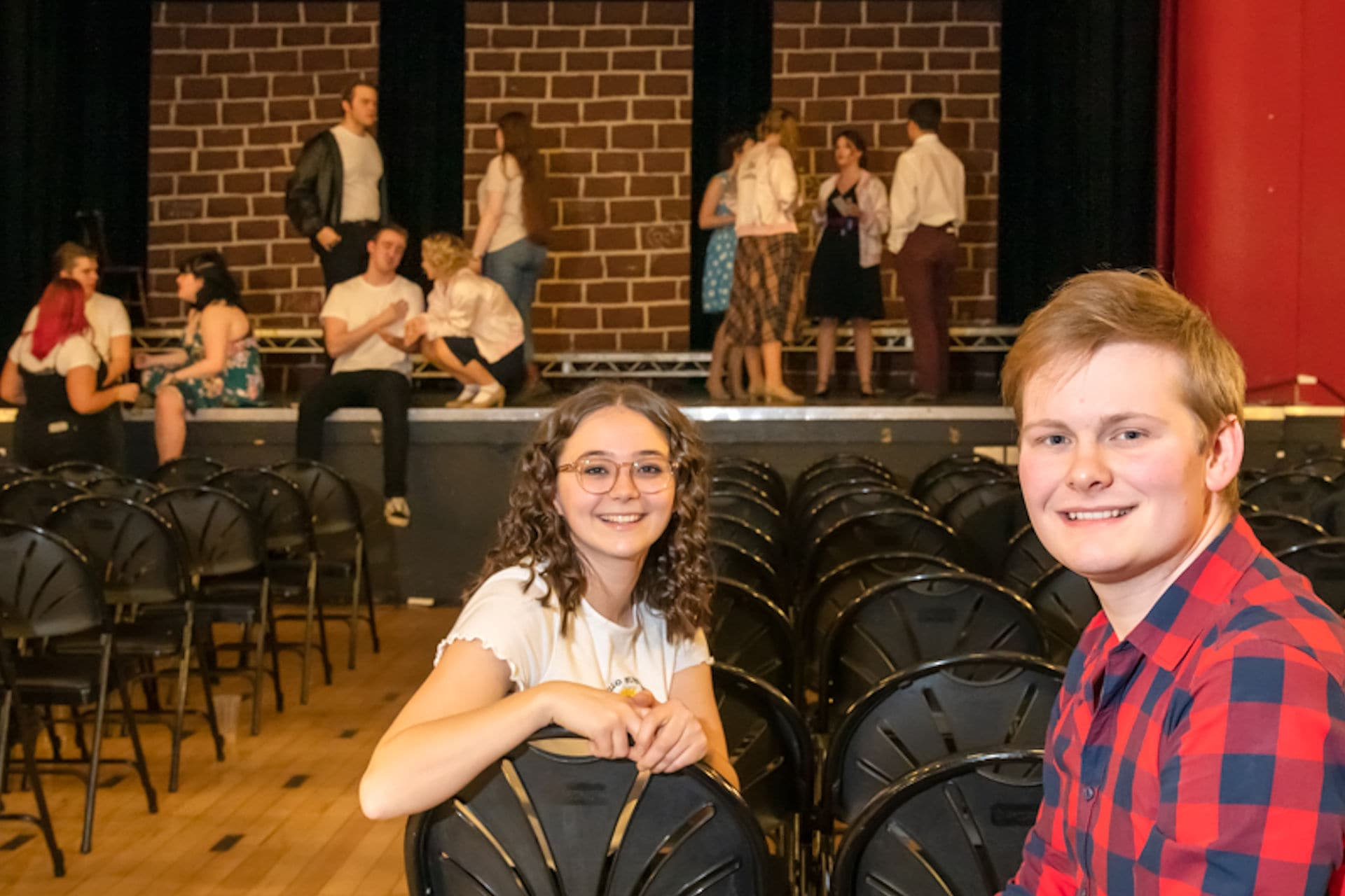 Students in theatre space smiling at camera with other students performing in background