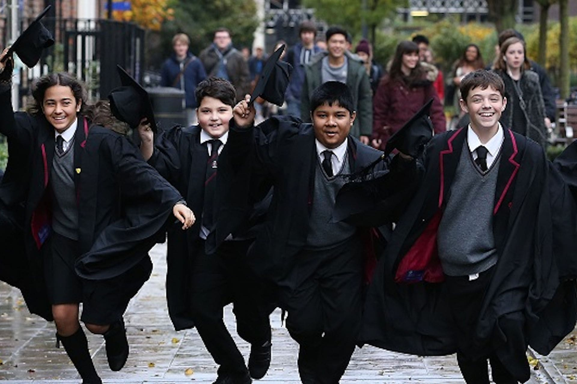 WP school students in cap and gown running towards camera smiling raising caps