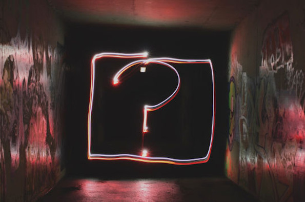 A question mark in neon lights surrounded by graffiti